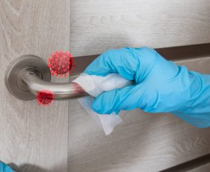 Wiping door knob with antibacterial disinfecting wipe for killing coronavirus. Coronavirus COVID-19. House cleaning and cleanliness